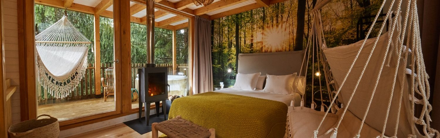 Hidden among tall fir trees, its design combines the sophistication of black accessories or gold-coloured taps with the exotic, safari-like atmosphere provided by cream colours, hammocks or lush vegetation in the surroundings.